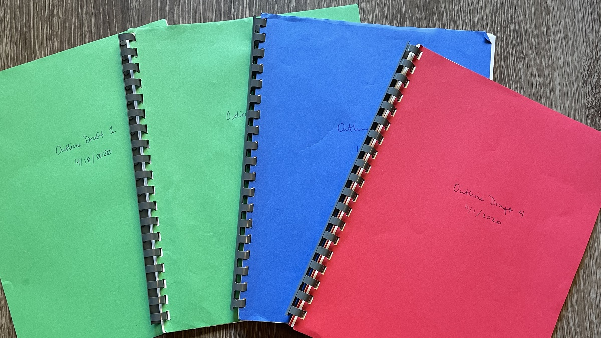 four bound sets of paper labeled Outline Draft 1 to 4
